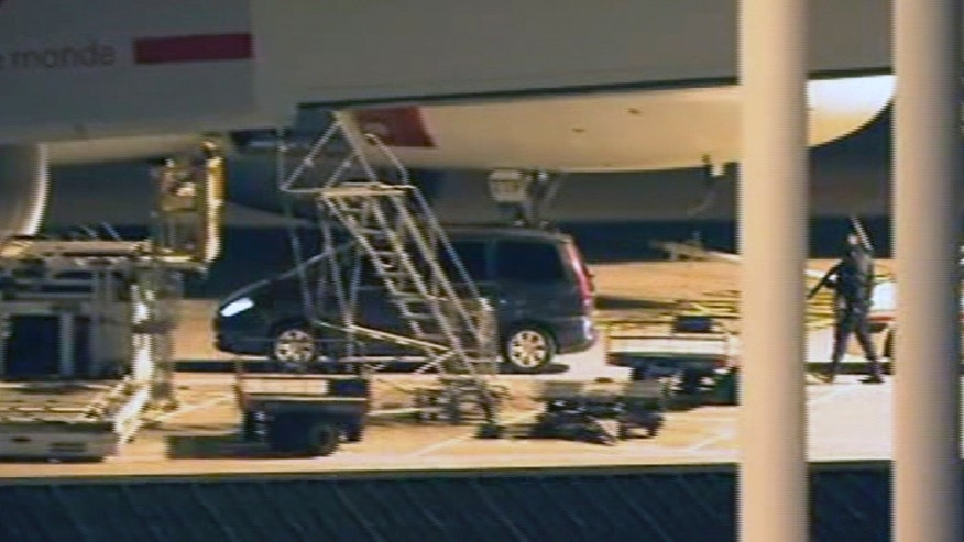 In this image from TV, showing tight security as a car carrying former Panamanian dictator, Manuel Noriega, approaches a plane at Orly airport, next to Paris, France, on Sunday, Dec.11, 2011.  Following a medical examination in France, the 77-year old former Panamanian strongman Manuel Noriega was pronounced fit enough to be extradited to his homeland of Panama which he fled in 1989. (AP Photo/APTV) TV OUT