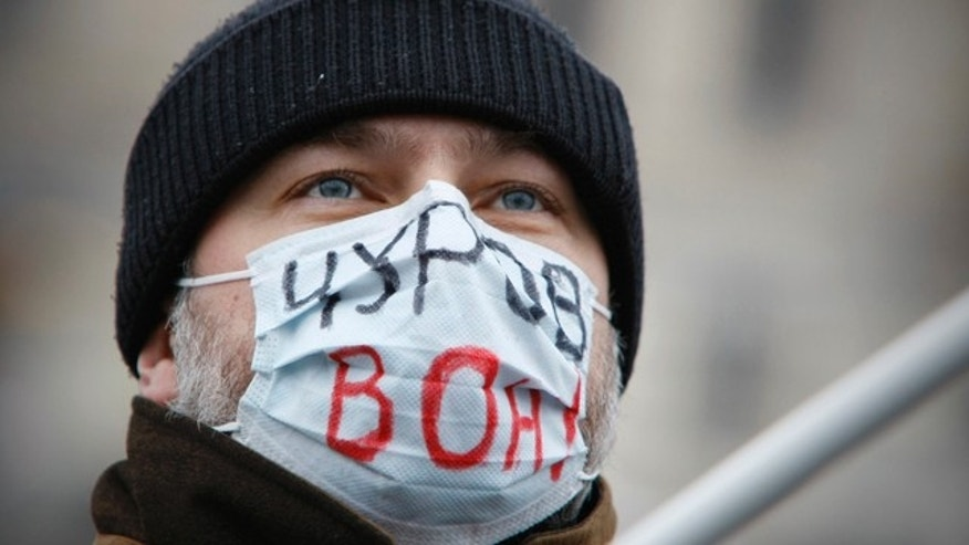 Dec. 11: A masked protesterwith the words 'Central Election Commission chief Vladimir Churov is a thief' during their rally at Bolotnaya Square, on an island in the Moscow River adjacent to the Kremlin.