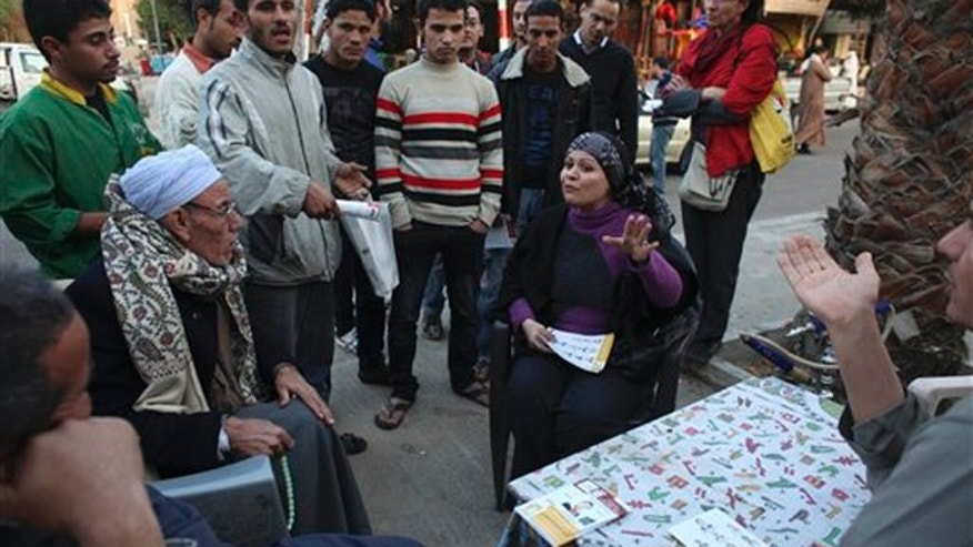 December 9, 2011: Egyptian Parliamentary candidate Abeer Hamdy, center right, sits with local residents as she campaigns in 6th of October, a suburb of Cairo.