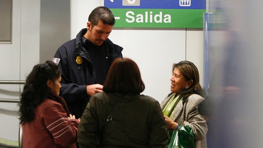 FILE - In this Dec. 29, 2010 file photo, a Spanish police officer asks for identification documents from immigrants inside a subway station in Madrid. Amnesty International is accusing Spanish police of widespread racial profiling, claiming they make identity checks based solely on people's ethnic or racial characteristics. In a report Wednesday Dec. 14, 2011, Amnesty says certain police stations in Madrid have weekly and monthly quotas for the number of irregular migrants they have to detain, encouraging officers to target people belonging to ethnic minorities.(AP Photo/Edu Leon, File)