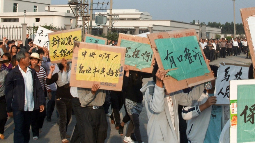Dec. 15, 2011: Villagers hold placards chanting slogans as they march around their village during a protest in Wukan village, in China's Guangdong province. A man from a southern Chinese fishing village whose death in police custody helped spark a rare revolt was given a hero's farewell Friday as thousands of tearful residents mourned what they called his sacrifice for them.