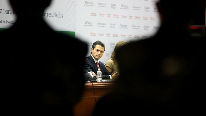 "Enrique Pena Nieto, former governor of Mexico State and the leading presidential candidate for the Institutional Revolutionary Party, PRI, attends the presentation event of his book, ""Mexico, la gran esperanza,"" or ""Mexico, the great hope,"" in Mexico City, Wednesday Nov. 23, 2011. Pena Nieto, who has led in all the recent national polls, seeks to regain the presidency his party lost in 2000 after 71 years in power. The presidential elections will take place in July 2012. (AP Photo/Alexandre Meneghini)"