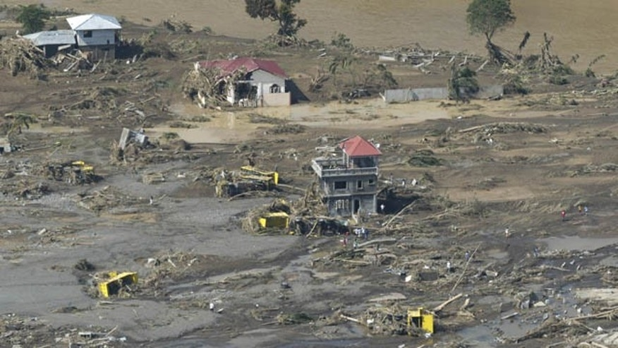 December 18, 2011: Remains of destroyed houses, toppled trucks and uprooted trees lie along a flood-hit area in Cagayan de Oro city, southern Philippines.