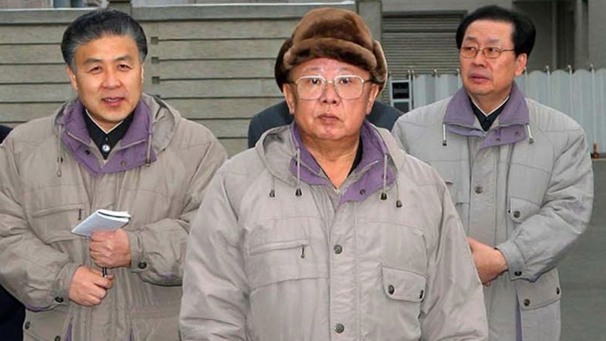 In this undated photo released by Korean Central News Agency via Korea News Service in Tokyo, North Korean leader Kim Jong Il, center, poses in front of the newly built Pothonggang Department Store in Pyongyang, North Korea.