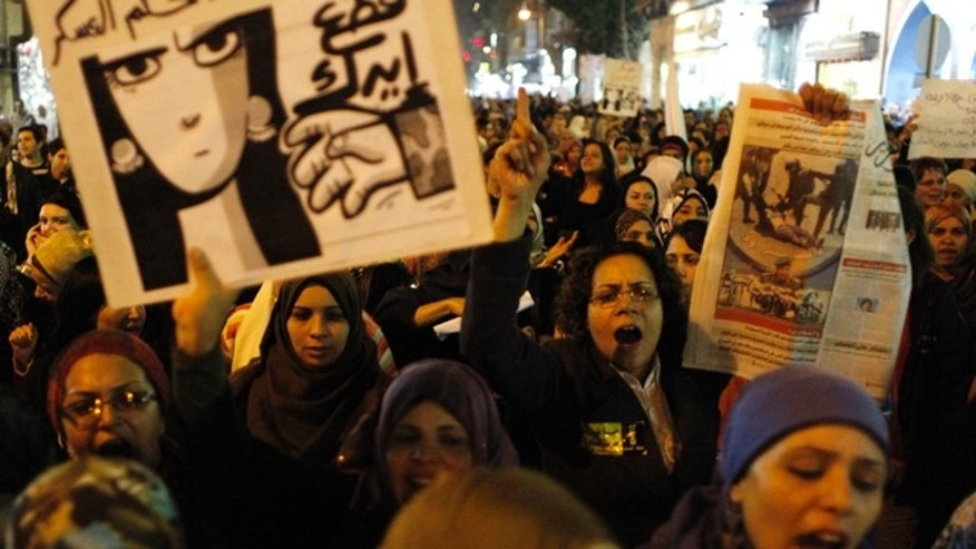 "Dec. 20, 2011: Egyptian women angered by the recent violence used against them in clashes between army soldiers and protesters, one carrying a poster that reads in Arabic ""Down with military rule, Military are liars and We will cut your hand"" chant anti military slogans during rally that ended in Tahrir Square, Cairo, Egypt."