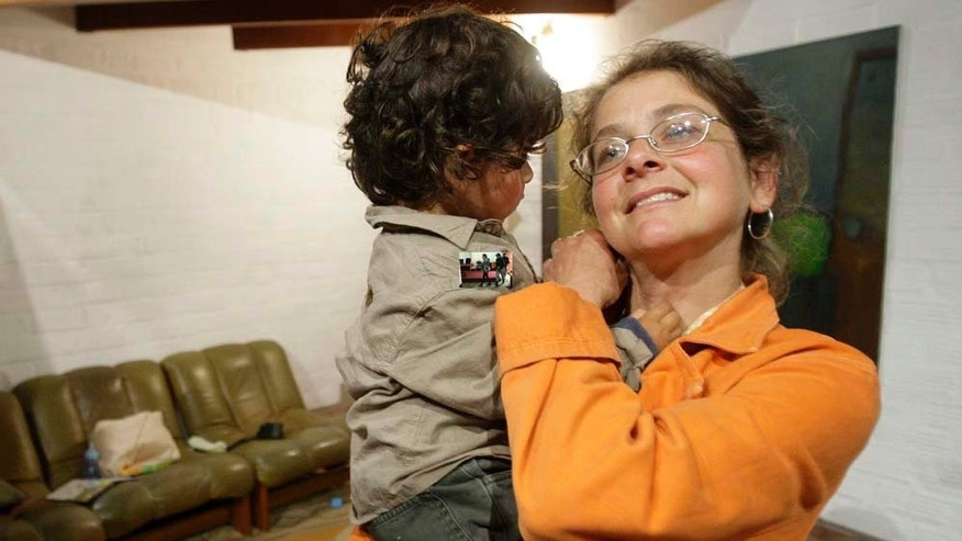 November 9. 2010: U.S. political activist Lori Berenson, right, holds her son  Salvador Apari as her mother Rhoda Berenson speaks on a cell phone after an interview with The Associated Press at her home in Lima, Perú.