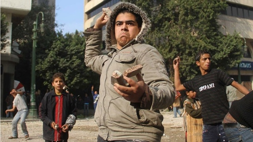 Dec. 16, 2011: Egyptian protesters throw rocks at military police during clashes near Cairo's downtown Tahrir Square, Egypt.