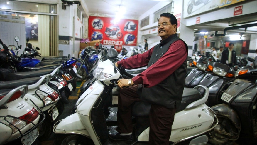Hari Kishan Pippal, 60, a member of India's outcast community once known as untouchables, sits on a scooter inside his Honda dealership showroom in Agra, India. Raised in poverty, he only made it through high school before his father became ill, and he had to go to work pulling a rickshaw to support the family.