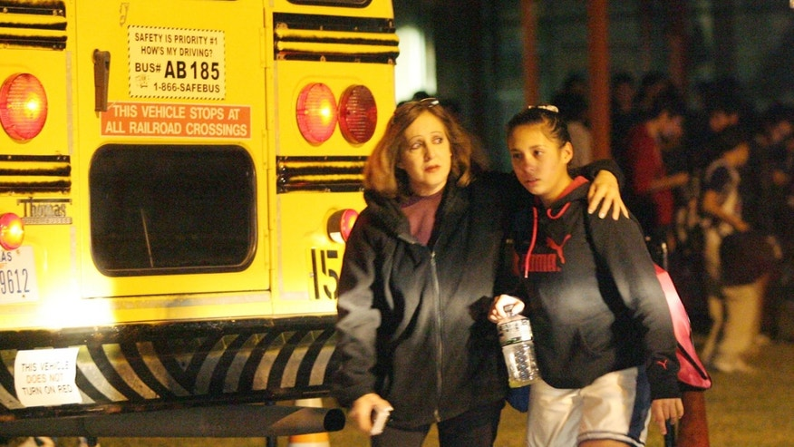 A mother picks up her daughter at Carmen Avila Elementary after a shooting at the nearby campus of Harwell Middle School in Edinburg, Texas. Authorities suspect hunters may have shot two South Texas middle school students who were wounded by gunfire while trying out for a basketball team.