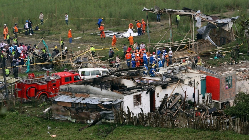 Dec. 23, 2011: People and rescue workers gather at the site of a pipeline explosion in Dos Quebradas, Colombia.