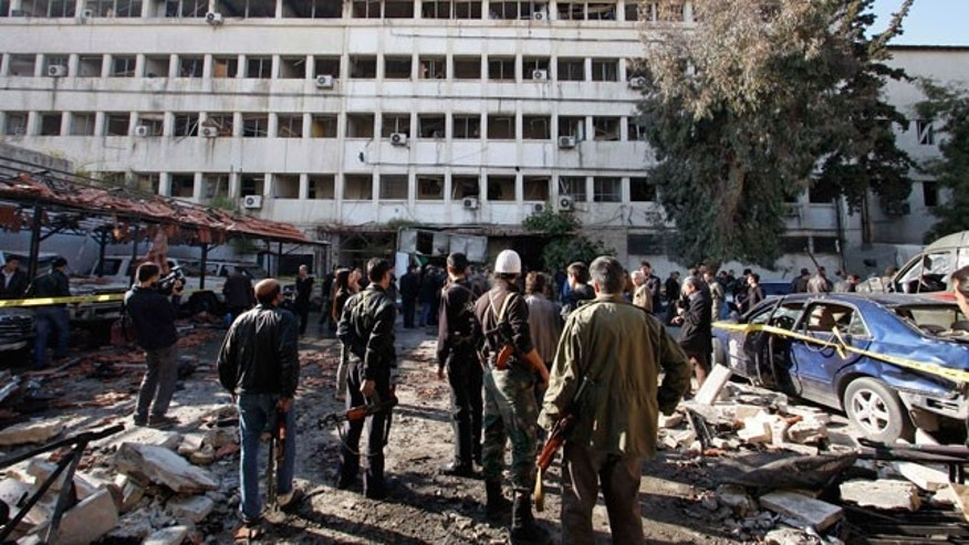 Dec. 23, 2011: People stand at the site of a suicide bombing in Damascus, Syria.