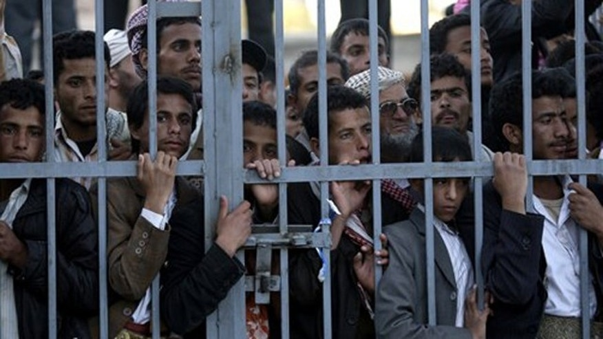 Dec. 24, 2011: Protestors stand behind the gate of a field hospital to watch wounded demonstrators being carried from the site of clashes with security forces, in Sanaa, Yemen.
