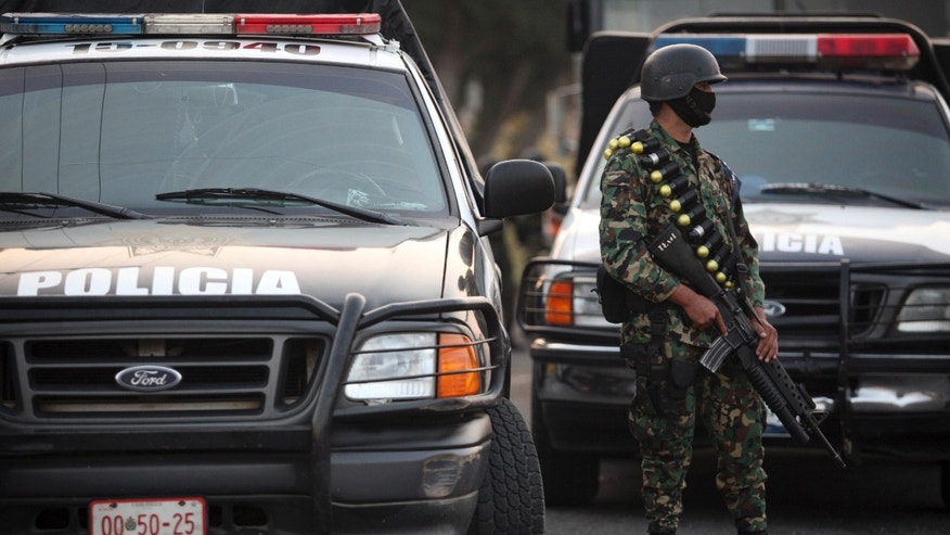 A masked Mexican navy marine keeps custody of police vehicles outside of a police station after the entire police force was disbanded in the Gulf port city of Veracruz, Mexico Wednesday Dec. 21, 2011. The Veracruz state government said the decision is part of an effort to root out police corruption and start from zero in the state's largest city. The navy will be in charge of patrolling the city for the time being. (AP Photo/Felix Marquez)