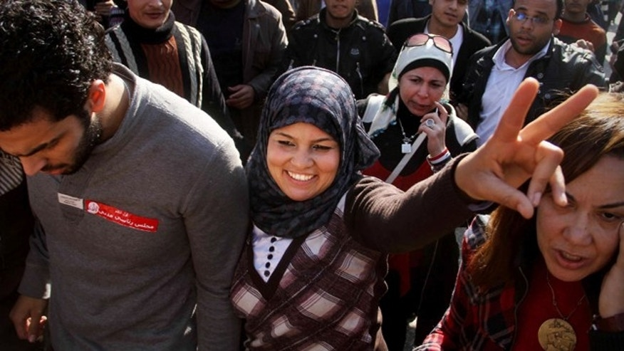 "Dec. 27, 2011: Samira Ibrahim, 25, flashes the victory sign during a rally supporting women's rights in Cairo, Egypt. An Egyptian court has ordered the country's military rulers to stop the use of ""virginity tests"" on female detainees, a practice that has caused an uproar among activists and rights. Ibrahim filed a lawsuit after being subjected to a forced 'test."""