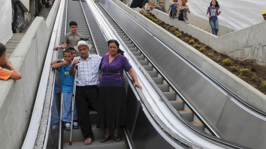 Luis Hernesto Holguin, front,  second from right, accompanied by relatives, uses outdoor escalators, newly installed at Comuna 13 shantytown as part of an urbanization plan to improve living conditions of residents, in Medellin, Colombia, Dec. 26, 2011. (AP Photo/Luis Benavides)