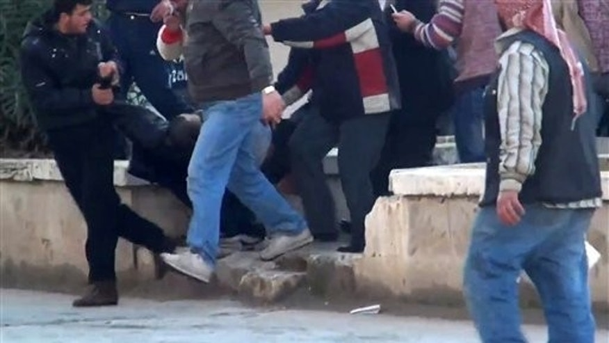 Dec. 30, 2011: This image made from amateur video and made available by Shaam News Network purports to show a wounded protester carried away by others in Idlib, Syria.