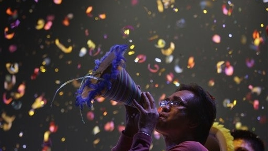 January 1, 2012: Confetti drops as a Filipino blows his paper horn as they welcome the New Year at Manila's Rizal Park, Philippines.