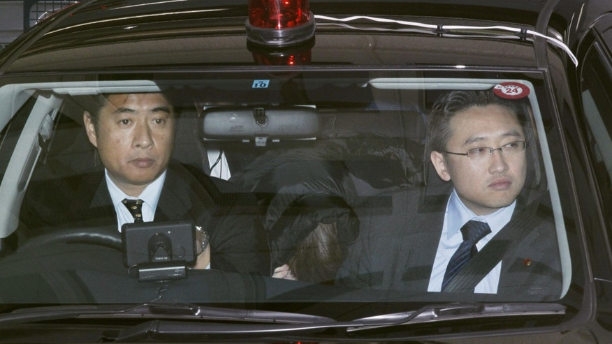 January 1: Makoto Hirata, a member of Aum Shinrikyo, rear center, sits in a police car as he is transferred to another police station in Tokyo. The member of the doomsday cult behind a deadly Tokyo subway gas attack and other crimes turned himself in to police after 17 years on the run, an official said.