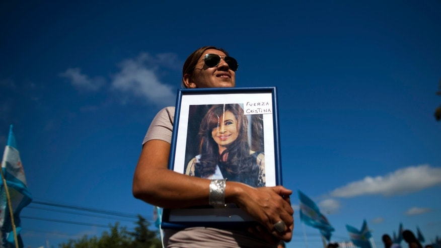 "Rosa Calderon holds a picture of Argentina's President Cristina Fernandez that reads in Spanish ""Be strong Cristina"" outside the hospital where Fernandez will  undergo surgery for thyroid cancer in Pilar, Argentina, Wednesday Jan. 4, 2012.  The 58-year-old leader has papillary thyroid carcinoma, and her doctors said it was detected before it spread, so her condition should curable without chemotherapy. Vice President Amado Boudou will be in charge during the operation on Wednesday and for 20 days as she recovers. (AP Photo/Natacha Pisarenko)"