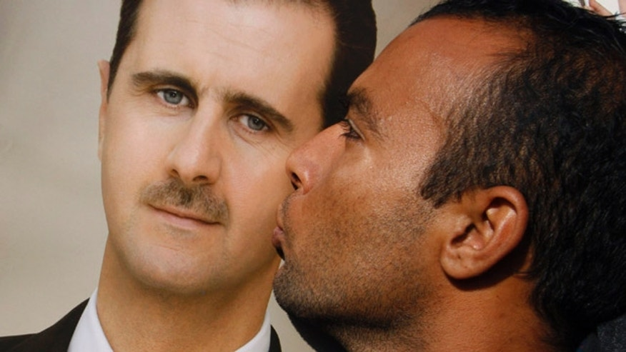 Jan. 4, 2012: A pro-Syrian regime protester kisses a portrait of Syrian President Bashar Assad during a demonstration in support of their President, in Damascus, Syria.