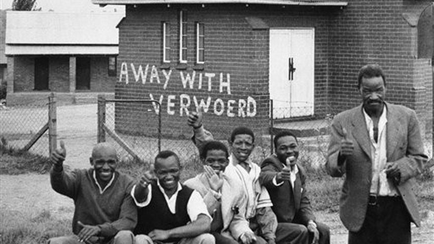 March 28, 1960: In this file photo, members of the African National Congress take part in a day of mourning at Orlando East, near Johannesburg, South Africa. The building in background has words 'away with Verwoerd' painted on it. Verwoerd was South Africa's Prime Minister and strong proponent of the racial policies that led to the mass shooting at Sharpesville.
