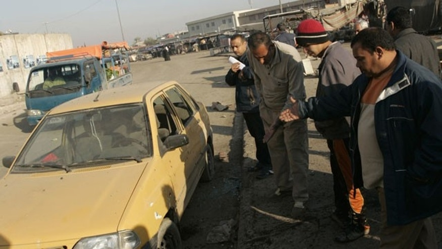 January 5, 2012: People gather at the site of a bomb attack in Sadr city, eastern Baghdad. Two bombs exploded in a mainly Shi'ite Muslim area of Iraq's capital killing six people and wounding 17, police and hospital sources said.