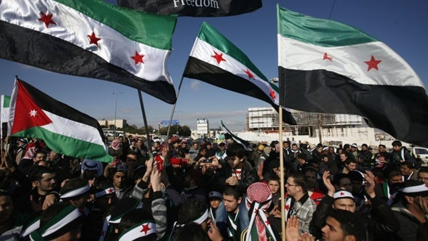 January 6, 2012: Syrians wave revolutionary flags during an anti-regime protest in front of the Syrian embassy in Amman, Jordan.