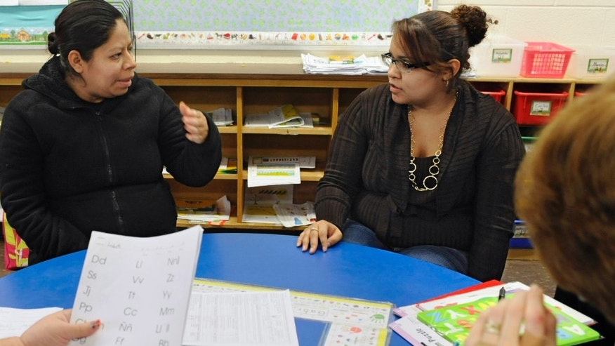 In this Friday, Dec. 2, 2011 photo, parent liaison Ana Lozada, second from right, translates Spanish to English for parent Blanca Salas, second from left, as bilingual teacher Millie Vera, left, and special education teacher Kathy Bentley meet with Salas during a parent-teacher conference for her daughter Lizbeth at Windham Center School in Windham, Conn. Connecticut's investment in teaching of English as a second language declined steadily over the last decade despite a 50 percent increase in the Latino population. (AP Photo/Jessica Hill)