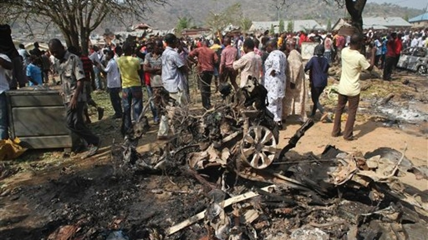 Dec. 25, 2011: Onlookers  gather around a car destroyed in a blast next to St. Theresa Catholic Church in Madalla, Nigeria after an explosion ripped through a Catholic church during Christmas Mass near Nigeria's capital.