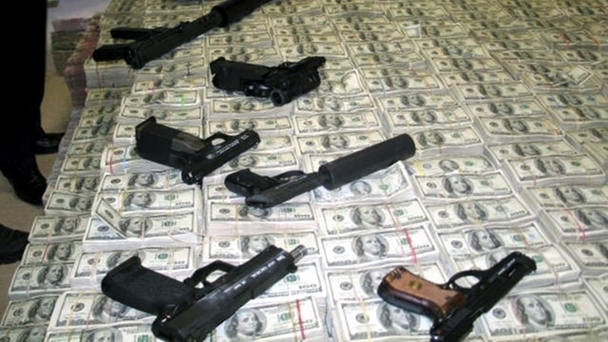 March 15, 2007: A haul of about $206 million is seen with confiscated weapons after the money was found stashed in closets, suitcases, and drawers in a house in an upscale neighborhood of Mexico City.