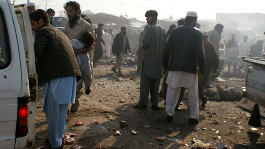 Jan. 10, 2012: A man carries an injured person to a vehicle after an explosion in Pakistani tribal area of Khyber near Peshawar, Pakistan.