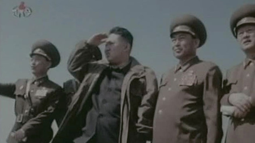 In this undated image made from KRT video, North Korea's new young leader Kim Jong Un, third from right, watches jet fighters with North Korean officials at an undisclosed place in North Korea.
