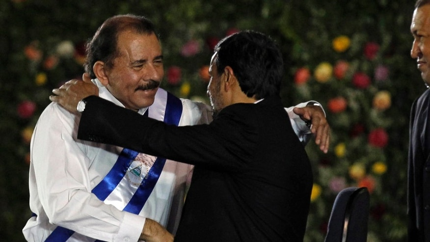 Nicaraguas President Daniel Ortega, left, is congratulated by Iran's President Mahmoud Ahmadinejad as Venezuela's President Hugo Chavez, right, looks on after Ortega was sworn in for a third term at the swearing-in ceremony in Managua, Nicaragua, Tuesday Jan. 10, 2012. (AP Photo/Esteban Felix)