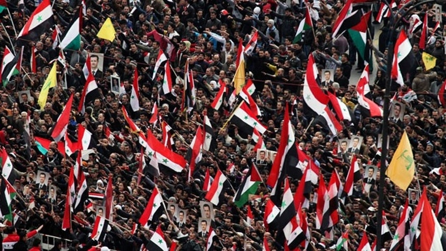 Jan. 11, 2012: Pro-Syrian regime protesters wave the national flag, as well as Hezbollah flags, in yellow, as they gather during a demonstration to show support for Syrian President Bashar Assad at a central square in Damascus, Syria.