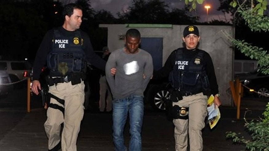 U.S. Immigration and Customs Enforcement (ICE) agents escort a man, center, after his arrest in connection with a document fraud case in San Juan, Puerto Rico, Wednesday Jan. 11, 2012. Fifty people have been accused of conspiring to sell the identities of hundreds of Puerto Ricans to illegal immigrants on the U.S. mainland in the largest individual fraud case ever for U.S. Immigration and Customs Enforcement, authorities said Wednesday. (AP Photo/El Vocero, Dennis A. Jones) PUERTO RICO OUT - NO USAR EN PUERTO RICO