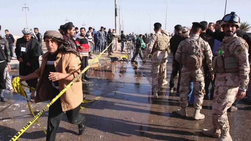 Jan. 14: Security forces and people inspect the scene of a bomb attack on Shiite pilgrims, killing and wounding scores of people, police said, near the southern port city of Basrah.