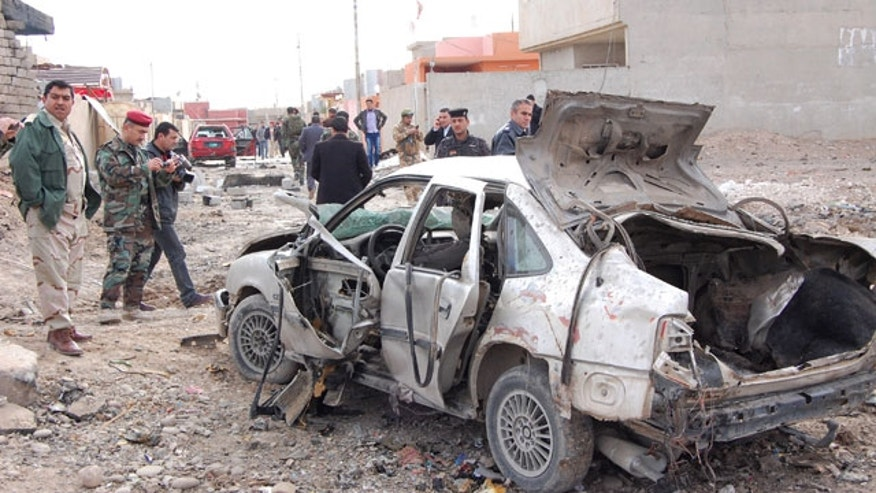 January, 16, 2012: Iraqi security forces inspect the scene of a car bomb attack outside the northern city of Mosul, 225 miles northwest of Baghdad, Iraq.