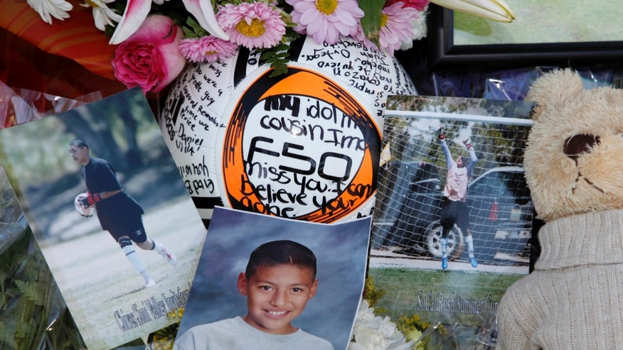 Photos of El Camino Real's goalkeeper Francisco Rodriguez, are seen next to a soccer ball at a memorial set outside his family's home in Los Angeles.