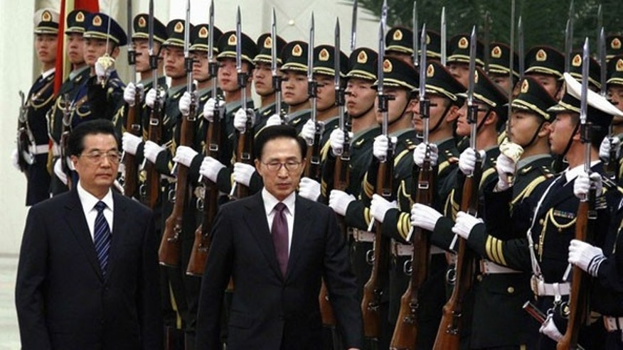 January 9, 2012: South Korean President Lee Myung-bak (2nd L) walks with Chinese President Hu Jintao (L) as they inspect a guard of honor during an official welcoming ceremony in the Great Hall of the People in Beijing.