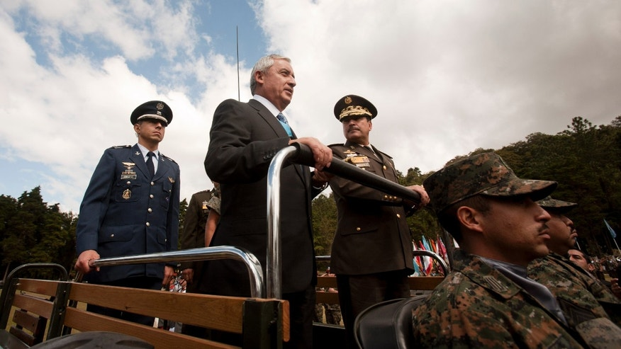 Guatemala's newly sworn-in President Otto Perez Molina, center, and Minister of Defense Ulises Anzueto Giron, right, review the troops during a military ceremony recognizing Perez as commander-in-chief, in Guatemala City, Sunday Jan. 15, 2012. Perez, a retired general, is the first military officer elected as Guatemalan president since the end of a military government 25 years ago. He served in that administration as director of intelligence. (AP Photo/Moises Castillo)