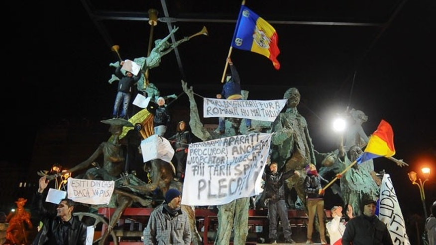 "Jan. 16, 2012: Anti-government protesters hold banners that read ""Leave"" or ""Come out of your houses if you care"" climbed on a group of statues in front of the national theatre, downtown Bucharest, Romania."