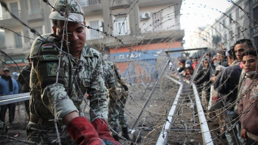 Nov. 24, 2011: An Egyptian soldier helps to put a barbed wire barricade in place, near Tahrir square in Cairo, Egypt.