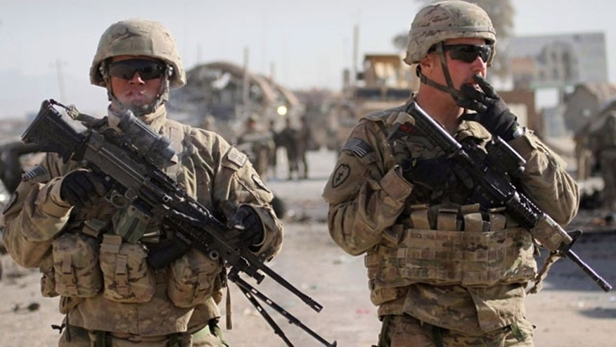 Jan. 19, 2012: U.S. soldiers with the NATO led International Security Assistance Force (ISAF) stand guard at the scene of a suicide attack in Kandahar south of Kabul, Afghanistan.