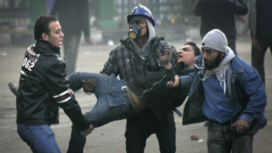 December 17, 2011: Egyptian protesters carry an injured fellow protester during clashes with military police near Tahrir Square in Cairo, Egypt.