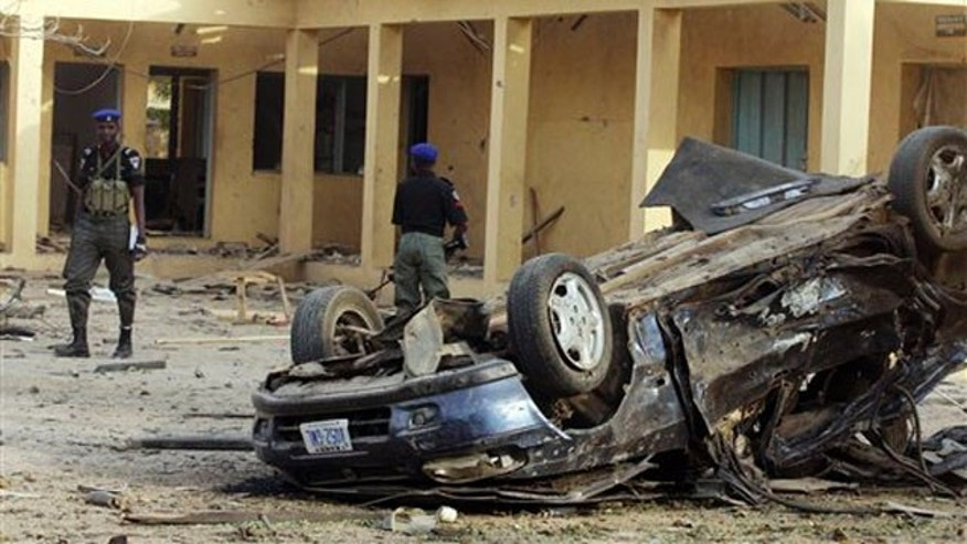 Jan. 22, 2012: Police stand guard at the site of the police headquarters bombed by a suicide bomber in Kano, Nigeria.
