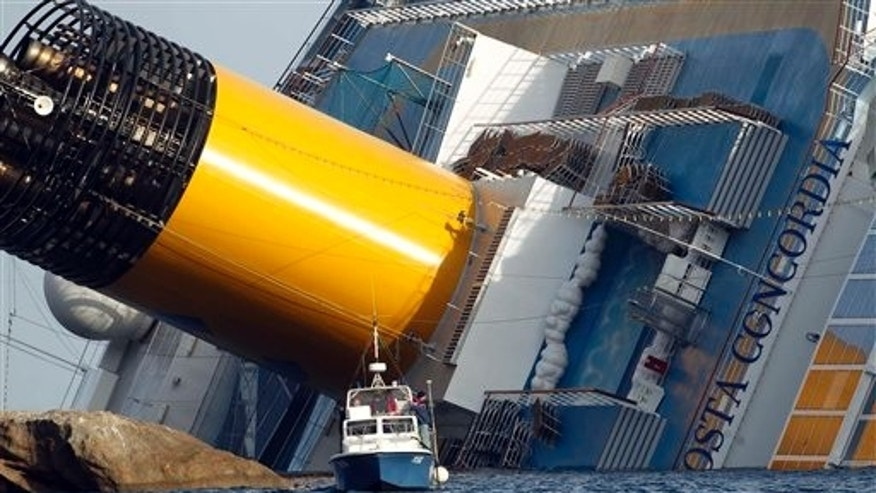 Jan. 22: A police boat sails by the grounded cruise ship Costa Concordia, off the Tuscan island of Giglio, Italy. Rescuers on Sunday resumed searching the above-water section of the capsized Costa Concordia cruise liner, but choppy seas kept divers from exploring the submerged part, where officials have said there could be bodies.