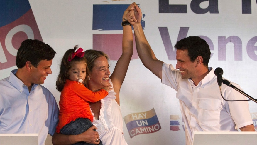 Opposition politician Leopoldo Lopez, puts his arm around the waist of his wife Lilian Tintori as she holds their daughter Manuela, 2, and raises her left hand with presidential candidate Henrique Capriles Radonski at a news conference in Caracas, Venezuela, Tuesday Jan 24, 2012. (AP Photo/Ariana Cubillos))