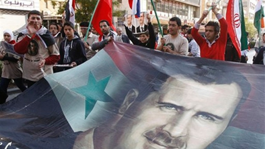Nov. 25, 2011: Pro-Syrian regime protesters shout slogans and carry a huge portrait of the Syrian president Bashar Assad during a protest against the Arab League decisions, in Damascus, Syria.