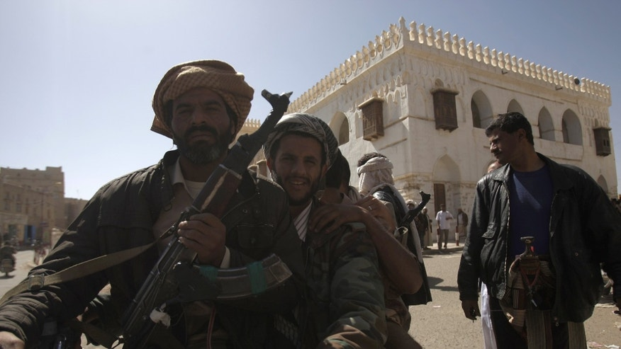 Jan. 25, 2012: Backdropped by Ameriyah religious school which was seized by Al Qaeda militants, a Yemeni armed tribesman, left, holds his rifle as he rides a motorcycle with others in Radda town, 100 miles south of the capital Sanaa, Yemen.