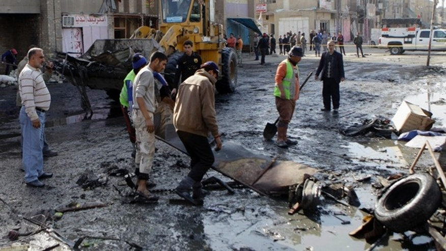 Jan. 27: People clean the scene of a car bomb attack in Zafaraniyah, Baghdad.